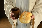 Jesus hands holding bread and wine over dark background poster