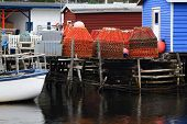 Dock for crab fishermen with stocked on pile Crab Nets in Petty Harbor Newfoundland Canada. poster