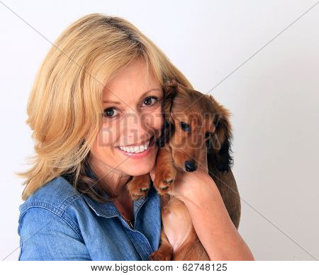 Blond lady holding a dachshund puppy.