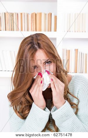 beautiful girl feeling ill caught cold sniffles blowing her nose into tissue poster