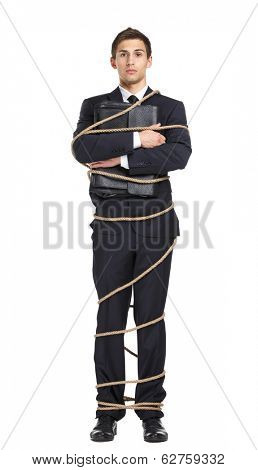 Full-length portrait of businessman handing briefcase who bound with the rope, isolated on white. Concept of slavery and violence