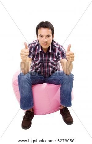 Young Casual Man Seated In A Small Pink Sofa Going Thumb Up