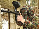 Military paintball player in swiss camo in action poster