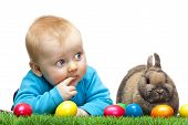 Cute young child is lying in meadow together with Easter bunny and colorful Easter eggs in meadow. Isolated on white Background. poster