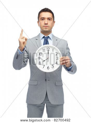 business, people, time management and gesture concept - businessman in suit holding clock showing 8 o'clock and pointing finger up