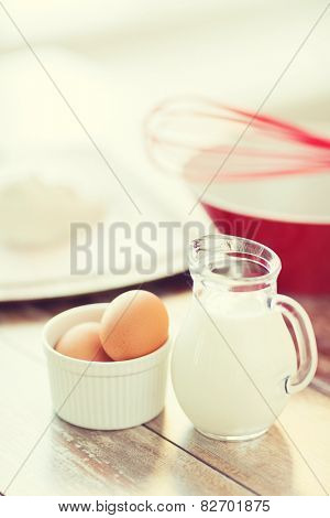 cooking and food concept - close up of jugful of milk, eggs in a bowl and flour
