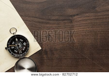 compass and old paper on the brown wooden table