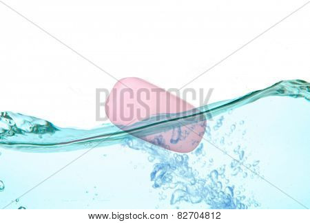 Aromatic pink soap in water splash isolated on white