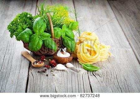 Italian Pasta Fettuccine Nest With Wicker Basket Of Green Herbs On Wooden Background