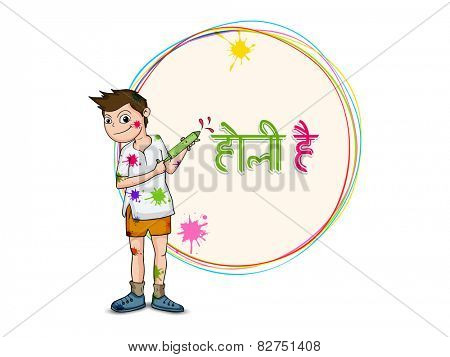 Cute little boy holding color gun (pichkari) on occasion of Indian festival, Holi celebration with Hindi text Holi Hai (Its Holi).
