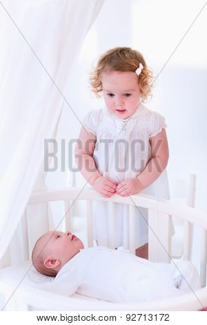 Kids in bed. Two children playing together in a white sunny bedroom. Little girl meets her newborn baby brother. Siblings play indoors. Infant boy in a white bassinet with his sister. Kid in a crib. poster