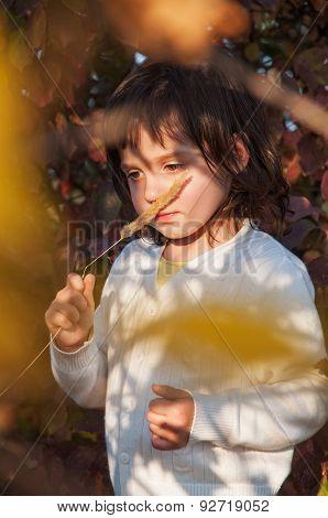 Dreamy little girl keep stalk of grass near the nose
