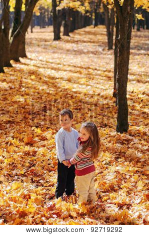 Smiling kids walk in the autumn park