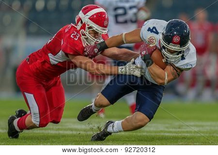 GRAZ, AUSTRIA - JUNE 2, 2014: WR Steve Delaval (#4 France) is tackled by LB Jimi Smidt Laursen (#23 Denmark).