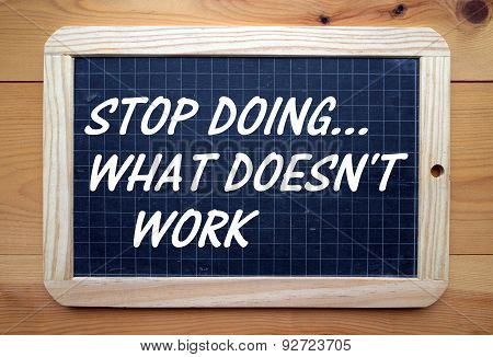 The phrase Stop Doing What Doesn't Work in white text on a blackboard. A reminder to change a process or direction in the event of failure. poster
