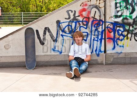 Boy Resting With Skate Board At The Skate Park