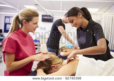 Teacher Helping Student Training To Become Masseuse