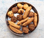 Indian savouries arranged in a vessel on a blurred background. (1) Chilly bajji (2) Dal vada (3) Aloo bonda are their commonly addressed Indian names. poster