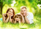 Happy joyful young family father, mother and little daughter having fun outdoors, playing together in summer park. Mom, Dad and kid laughing, lyying on green grass, enjoying nature outside. Sunny day poster