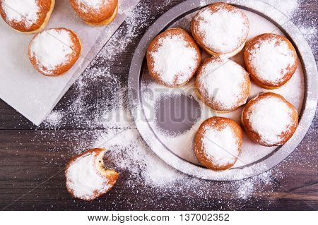 German donuts - berliner with jam and icing sugar in a tray on a dark wooden background. Top view