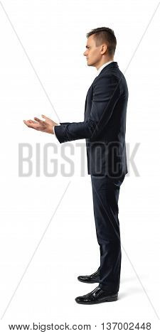 Side view of businessman holding something in his hands in front of him, isolated on white background. Successful lifestyle. Business staff. Office clothes. Dress code. Presentable appearance.