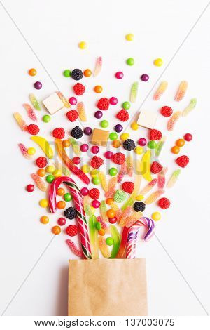 Colorful candies jellies and lolly pops spill out of the package on the white background. Top view