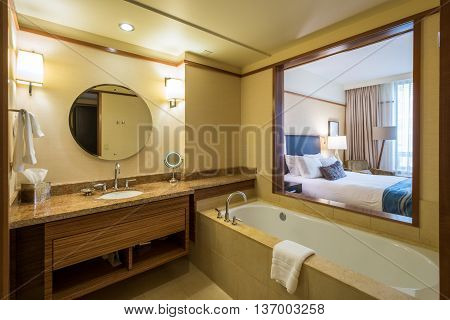Interior design of a spacious luxury bathroom with a window into the bedroom.