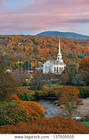 Stowe at sunset in Autumn with colorful foliage and community church in Vermont