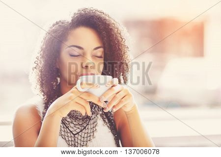 Bliss. Dreaming and happy young woman holding a cup of warm tea while relaxing with eyes shut