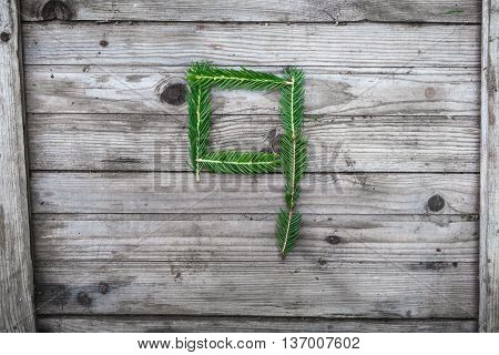 Number 9 from fir tree branches on aged wooden boards