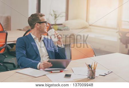 Dreaming one. Smiling and dreaming businessman sitting in the office while holding a digital tablet and drinking coffee