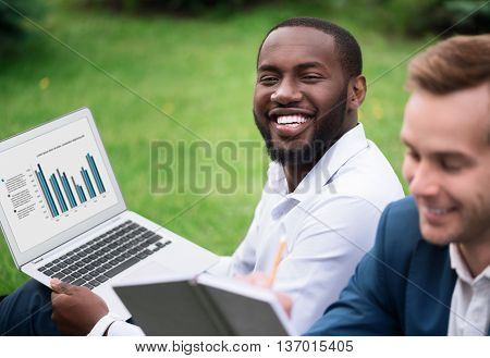 Evince your emotions. Cheerful delighted handsome smiling man sitting on the grass and holding laptop while resting with his colleague