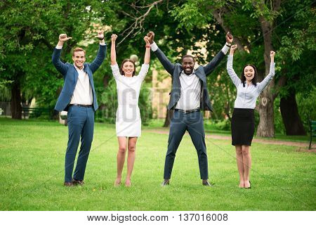 We are the winners. Positive delighted smiling colleagues holding hands up and expressing joy while standing on the grass