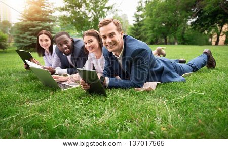 Change the surrounding. Positive glad smiling colleagues lying on the grass and using laptop while resting