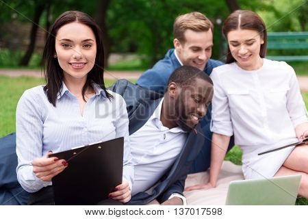 Happy to work together. Positive delighted smiling beautiful woman holding folder and sitting on the grass with her colleagues who is using laptop