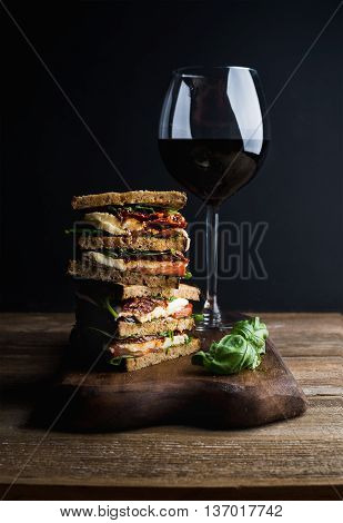 Caprese sandwich or panini and glass of red wine on wooden board. Whole grain bread, mozzarella cheese, dried tomatoes and basil. Dark background, vertical composition
