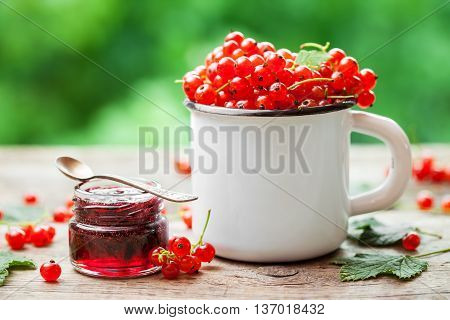 Mug Of Red Currant Berries And Jar Of Redcurrant Jam On Table Outdoors