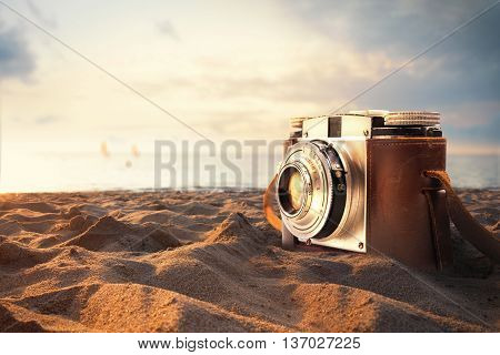 Vintage photo camera on the sand at the beach