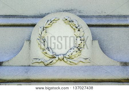 Ornate wreath and ribbons cast in stone on granite monument