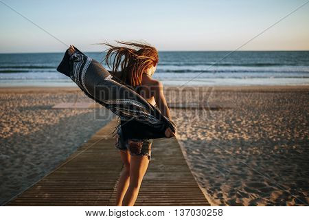 Back view of unrecognizable girl walking on wooden path on beach against of blue sky and sea in windy weather