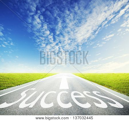 Asphalt road through the green field and clouds on blue sky in summer day and the word: success, on the road
