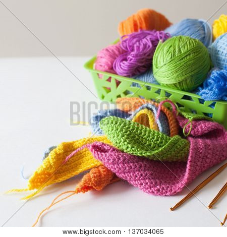 Balls of colored yarn. View from above. All the colors of the rainbow. Sample knit. Crochet.