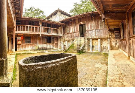 Ha Giang, Vietnam - September 21st, 2015: House ancient architecture with wood, handmade stone shelf, the front stone wells adorn home, where it recognized world material heritage in Ha Giang, Vietnam