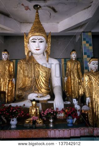 RANGOON / MYANMAR - CIRCA 1987: Sculptures of the Buddha sit at the Shwedagon Buddhist Pagoda in Rangoon.