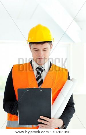 Portrait of a serious male architect holding blueprints