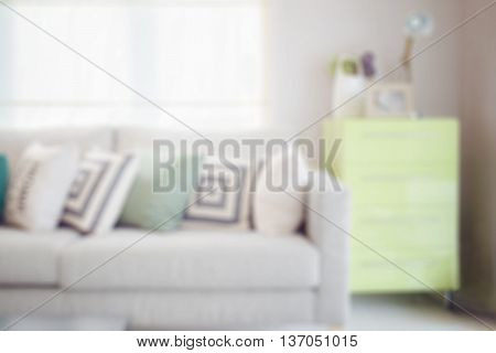 Blur Image Of Cozy Sofa With Geometric Pattern Pillows And Green Sideboard In Living Corner