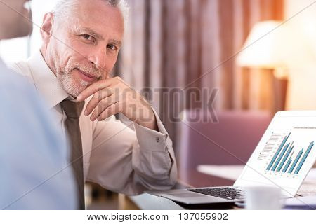 Confident glance. Pleasant delighted senior man sitting at the table and holding his hand near chin while using laptop