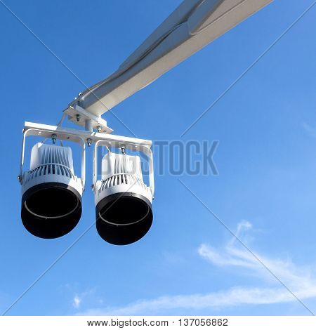 Two halogen spotlights with mechanical arm against blue sky.