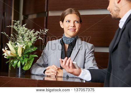 Friendly hotel receptionist and business guest at check-in