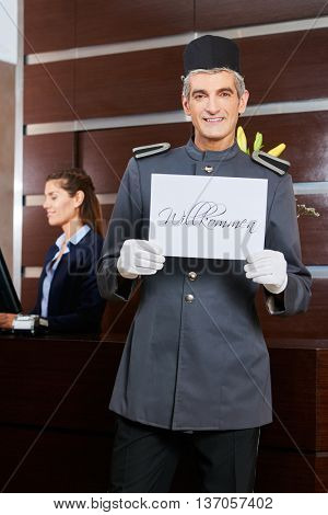 Smiling hotel concierge holding sign saying in German